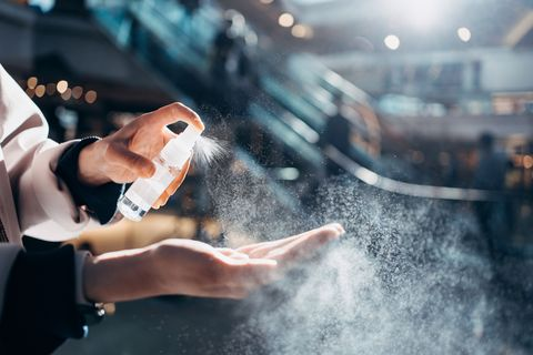 close up of young asian woman sanitizing her hand with disinfectant spray while shopping in a shopping mall against sunlight, with escalator and shoppers in background