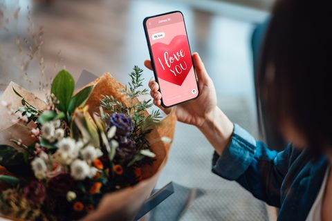 over the shoulder view of a unrecognisable woman receiving flower bouquet and reading i love you message on mobile phone online dating concept long distance relationship concept remote love