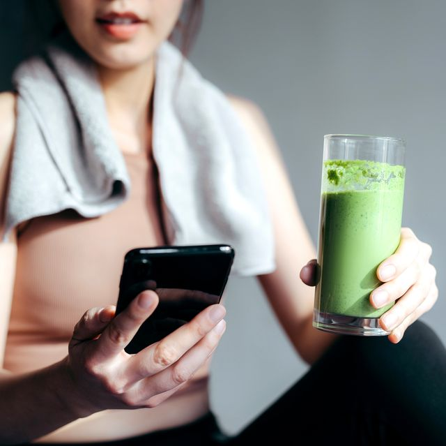 close up of confidence young asian sports woman taking a break, refreshing with healthy green juice and using smartphone after fitness work out  exercising  practicing yoga at home in the fresh bright morning