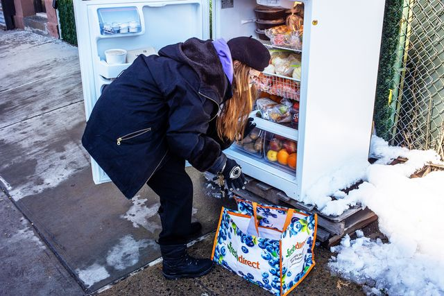 woman in snow in front of community fridge
