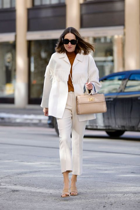 munich, germany   february 14 influencer annette weber wearing cream colored pants by seductive, a cream colored jacket with fringe details by sandro, a brown turtleneck pullover by mango, beige sandals by hm, a beige bag with fringe and gold details by bally and sunglasses by azzedine alaia paris eyewear during a street style shooting on february 14, 2021 in munich, germany photo by streetstyleshootersgetty images
