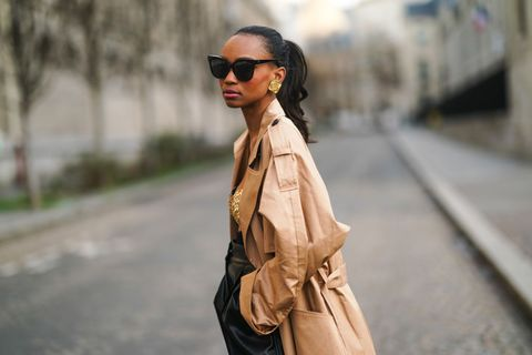 paris, france   february 17 emilie joseph wears sunglasses, golden earrings, a beige trench coat from gestuz, bronze shiny metallic bras from paco rabanne, black leather cropped pants from sportmax, on february 17, 2021 in paris, france photo by edward berthelotgetty images