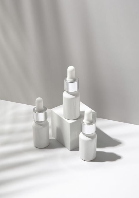 white cosmetic bottles with palm leaf shadow on white background blank label for branding mock up