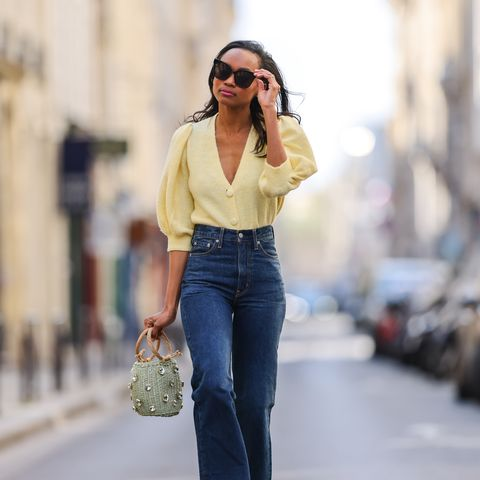 paris, france   april 03 emilie joseph infashionwetrust wears sunglasses, pale pastel yellow a puffed sleeves cardigan from mango, high rise blue denim jeans pants from levis, a lime green embellished bejeweled basket straw bag with top handle, on april 03, 2021 in paris, france photo by edward berthelotgetty images