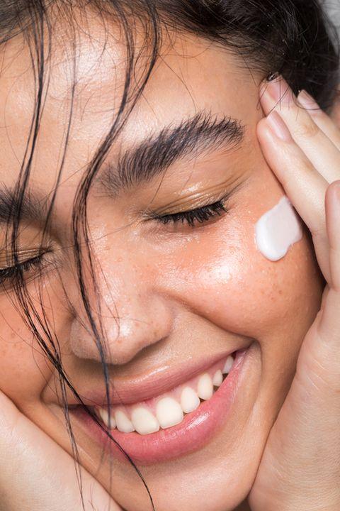 close up studio shot of a beautiful woman with perfect skin, she applying cream at cheek