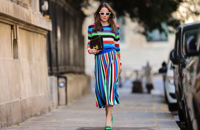 paris, france   april 08 therese hellström tesshell wears white cat eye sunglasses, a multi colored striped wool midi dress with long sleeves, a brown leather hermes bag, green pointed shoes with metallic pearls, on april 08, 2021 in paris, france photo by edward berthelotgetty images