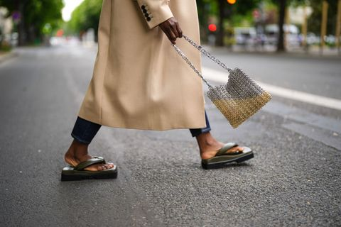 paris, france   may 02 carrole sagba linaose wears navy blue denim jean levis boyfriend pants, khaki shiny leather platform sole sinobio sandals, a long oversized givenchy coat with black buttons, a shiny silver and gold nails paco rabanne handbag, on may 02, 2021 in paris, france photo by edward berthelotgetty images