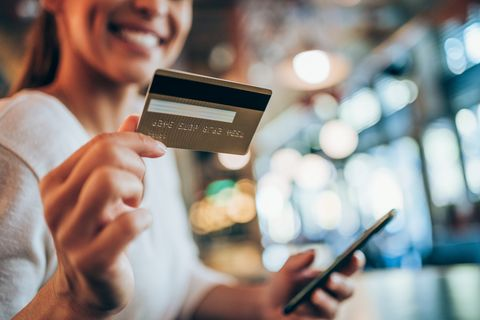 portrait of young woman doing shopping online with smartphone and payment by credit card woman holding smartphone and credit card in urban cafe focus is on the card