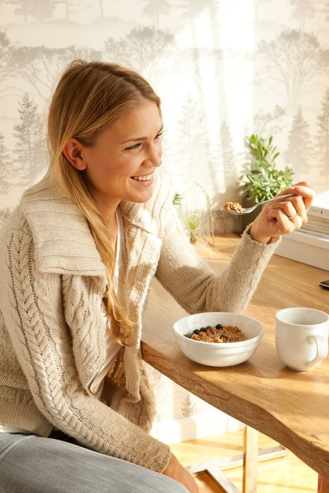 female having bowl of granola and coffee