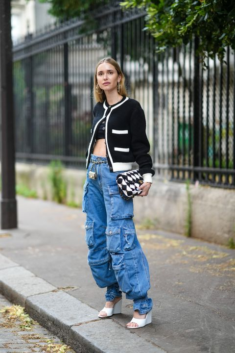 paris, france   july 06 pernille teisbaek wears silver pearls earrings from chanel,  black crop top, a black with white borders chanel cardigan, a black and white checkered with flower pearls embroidered handbag from chanel, a gold metallic pocket belt from chanel, blue denim large jeans cargo pants, white leather open toe cap wedge heels shoes, outside chanel, during paris fashion week   haute couture fallwinter 20212022, on july 06, 2021 in paris, france photo by edward berthelotgetty images