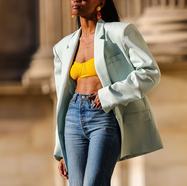 paris, france   july 17 emilie joseph infashionwetrust wears a pastel green oversized blazer jacket from the frankie shop, a yellow bralette  bra  bikini top, high waisted ribcage denim jeans by levi's, bold red mesh sandals by bottega veneta, colored vintage ceramic earrings, on july 17, 2021 in paris, france photo by edward berthelotgetty images