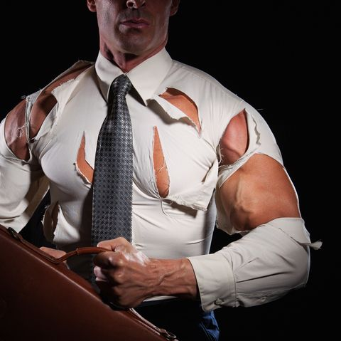 muscular businessman ripping his shirt by flexing his muscles