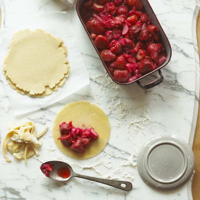overhead view of a strawberry hand pie being prepared on marble background