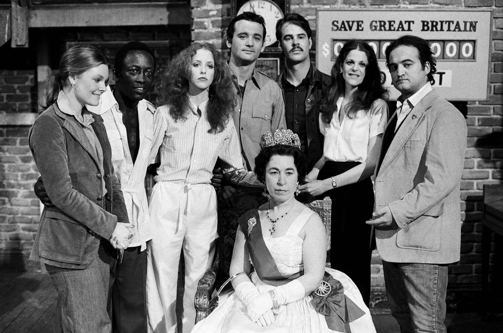 Jane Curtin, Garrett Morris, Laraine Newman, Bill Murray, Dan Aykroyd, Gilda Radner, John Belushi, and Jeanette Charles as Queen Elizabeth during the SNL 'Save Great Britain Telethon' skit on April 23, 1977.