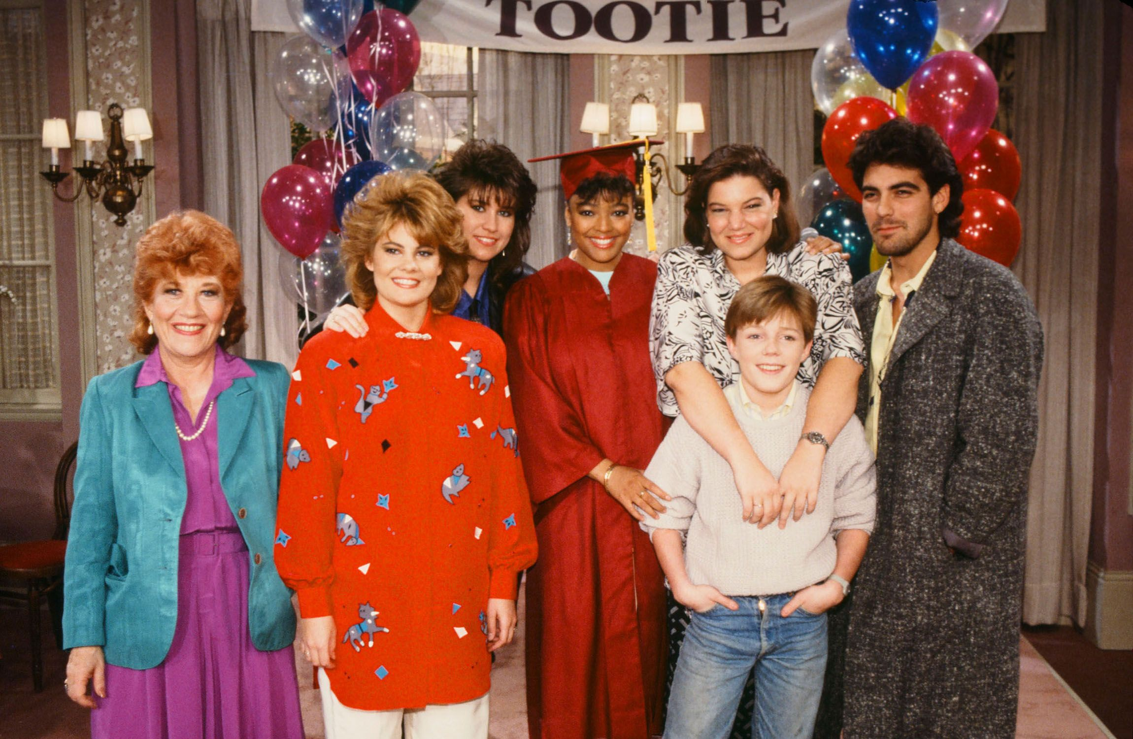 The Facts of Life cast at its 150th Show Party in 1986. Pictured: (L-R) Charlotte Rae as Edna Garrett, Lisa Whelchel as Blair Warner, Nancy McKeon as Joanne 'Jo' Polniaczek, Kim Fields as Dorothy 'Tootie' Ramsey, Mindy Cohn as Natalie Green, Mackenzie Astin as Andy Moffet, Clooney as George Burnett.