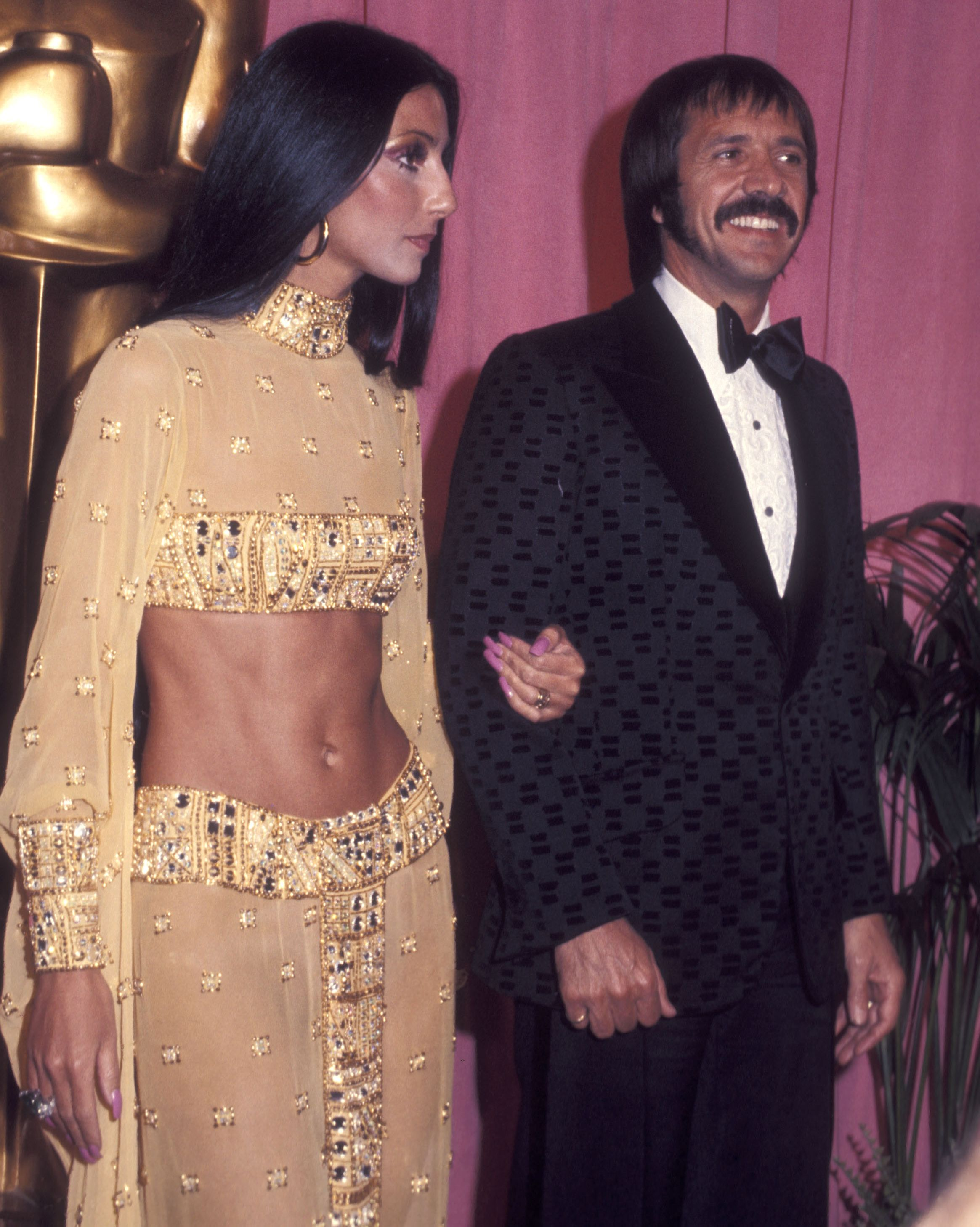 Cher dons a golden two-piece on the arm of her husband and singing partner, Sonny Bono.