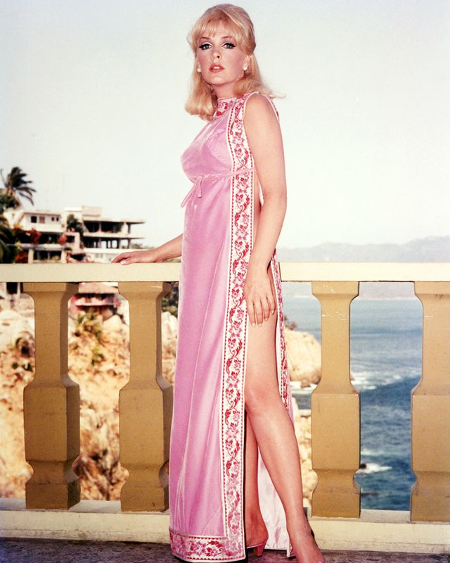 full length shot of stella stevens, us actress, wearing a pink silk dress, with her left leg exposed through a split in the skirt, as she poses leaning on a balustrade, circa 1960 photo by silver screen collectiongetty images