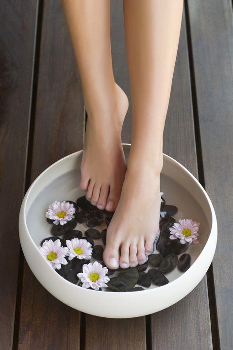 Woman enjoying foot bath, cropped