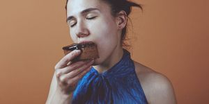 Woman eating chocolate pie, eyes closed