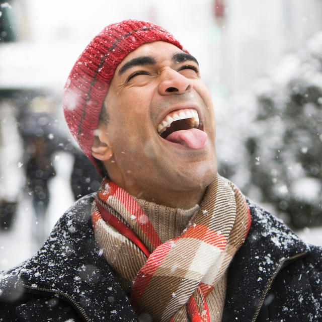man catching snowflakes with tongue