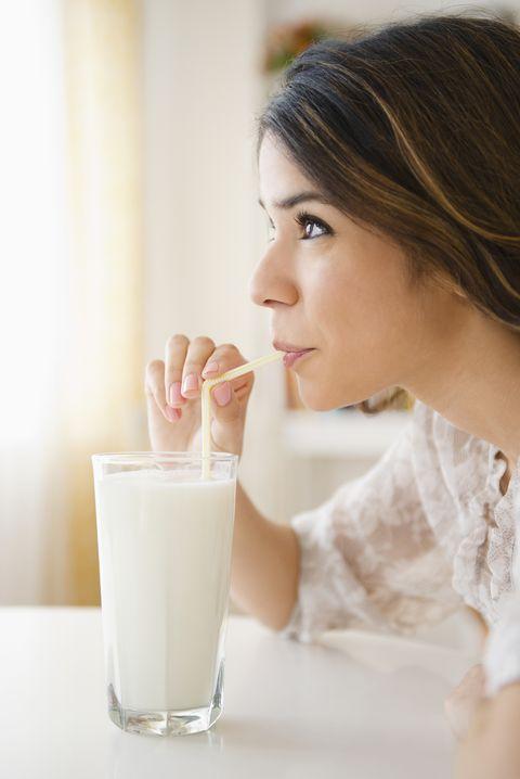 Hispanic woman drinking milk through straw