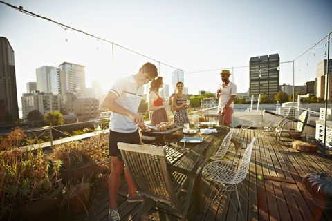 group of friends standing around table set for dinner on rooftop deck man checking barbecue at sunset