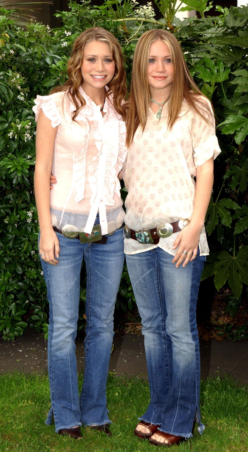 May 8, 2002 While presenting funds to a charity in London, the twins both wore cream colored tops with a chunky belt and flared blue jeans.
