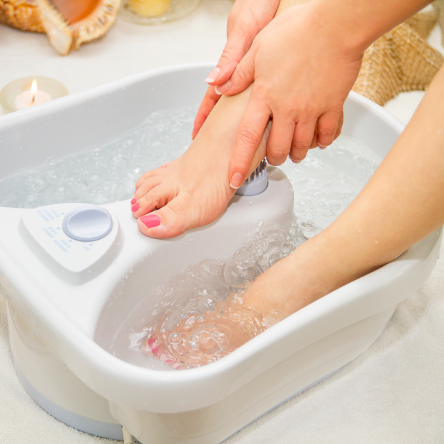 woman soaking feet in foot bath massager