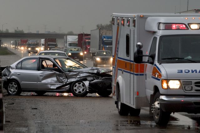 car crash on major highway during rainfall at night ambulance in foreground and police car in background