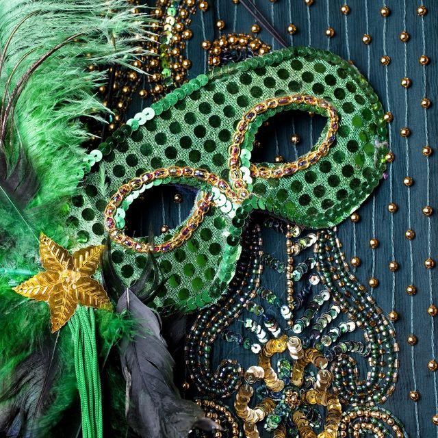 Mardi Gras mask on beaded green background.