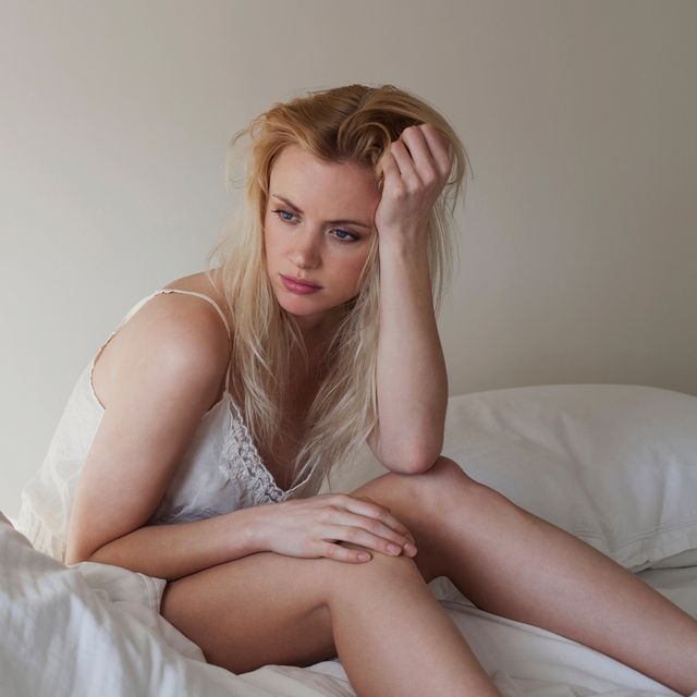 upset young woman sitting on bed