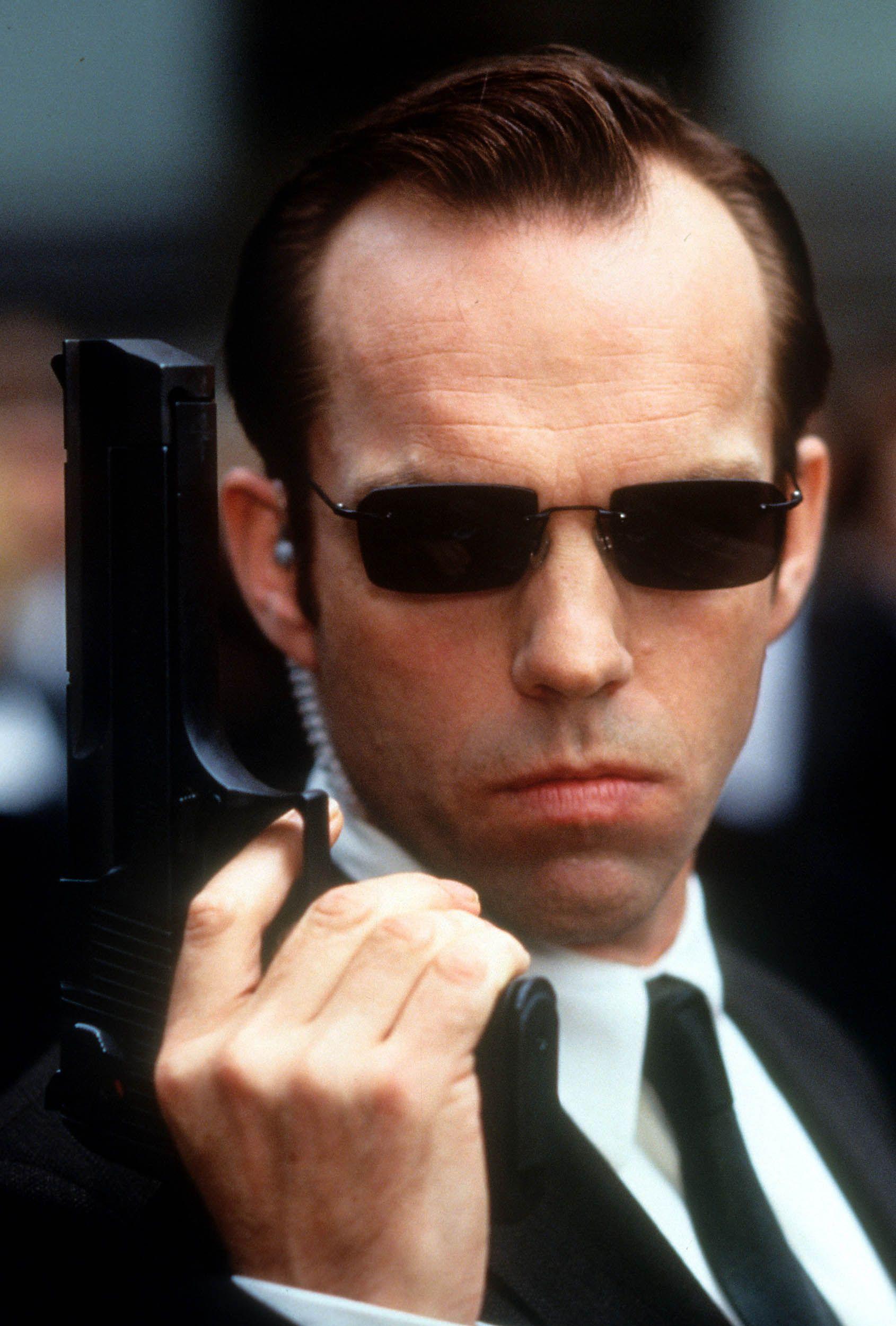 Hugo Weaving holding pistol in a scene from the 1999 film The Matrix.