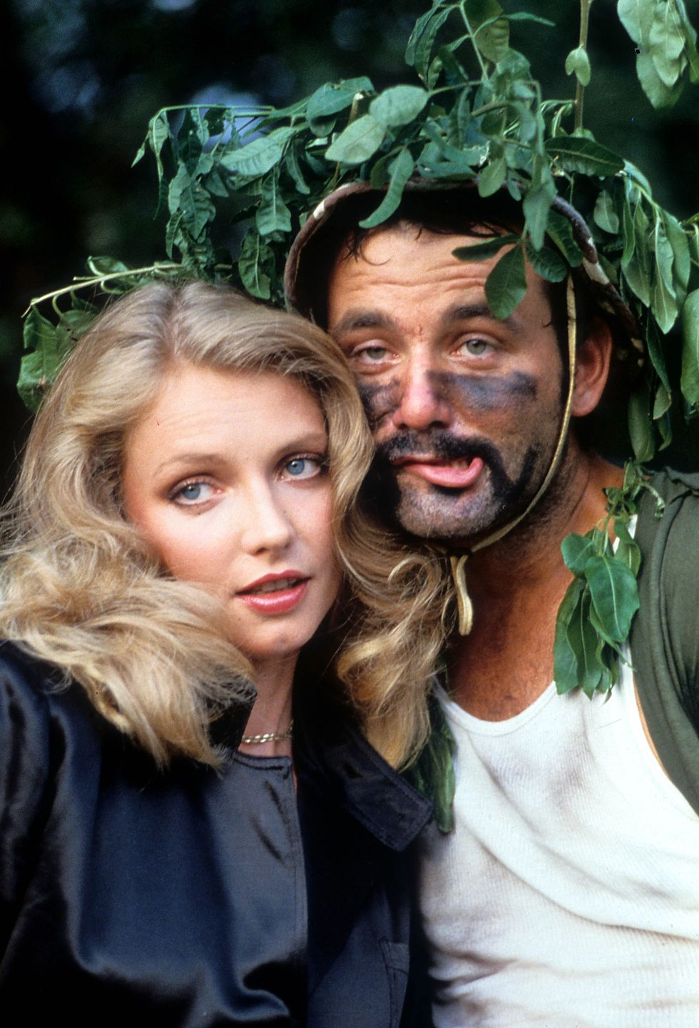 Cindy Morgan and Bill Murray nestled behind a tree in a scene from the film Caddyshack , 1980.