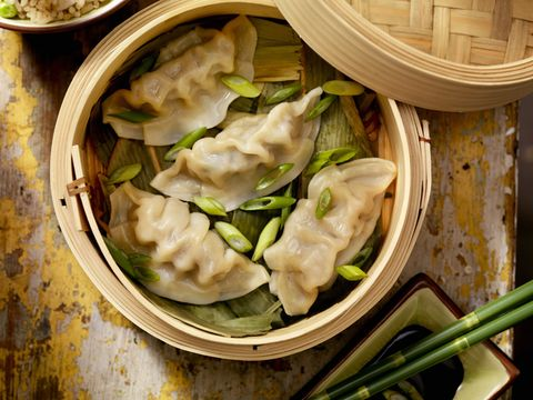 steamed dumplings in a bamboo steamer with bamboo leaves, fresh green onions, soya sauce and rice  photographed on hasselblad h1 22mb camera