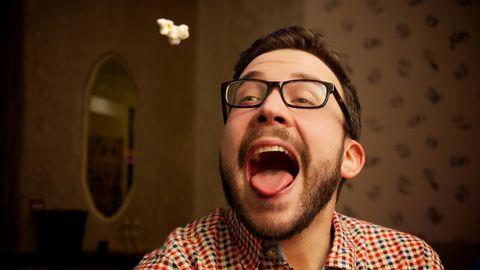 man probeert een stukje popcorn te vangen met zijn mond