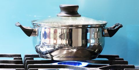 Saucepan boiling on gas stove with steam jet rising