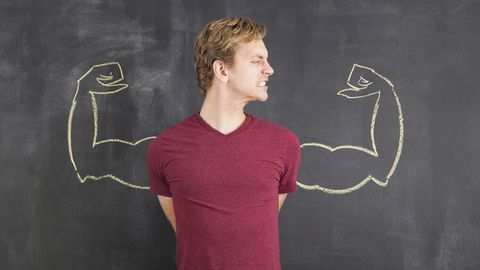 Studio shot of mid adult man with hands behind back and chalk drawing of artificial arms on blackboard