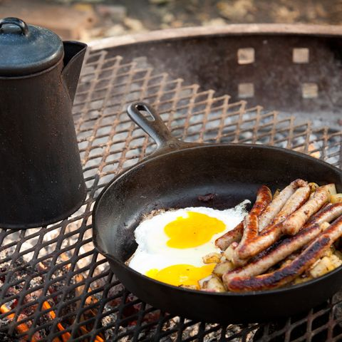 Cooking breakfast sausage & eggs on campfire outdoors with cast iron
