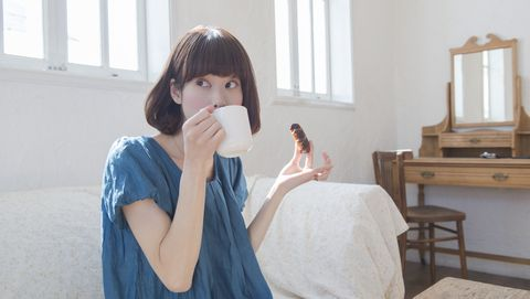 japanese woman eating snack and drinking a coffee