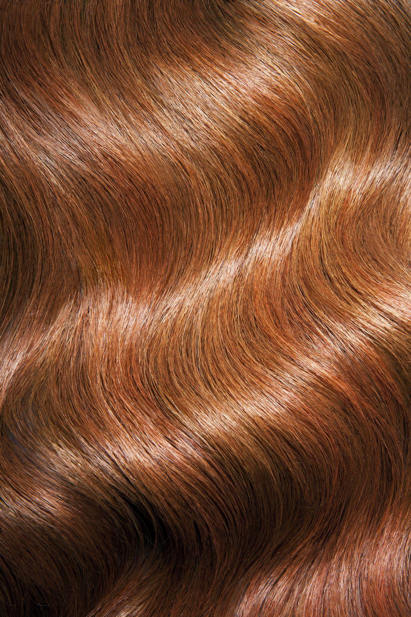 Tight shot of wavy, shiny red hair.