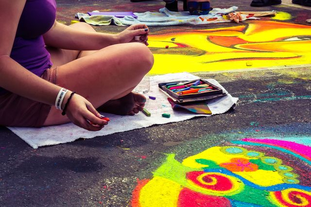 teenagers participating in the lake worth street art festival they are using chalk to make the drawings  rr