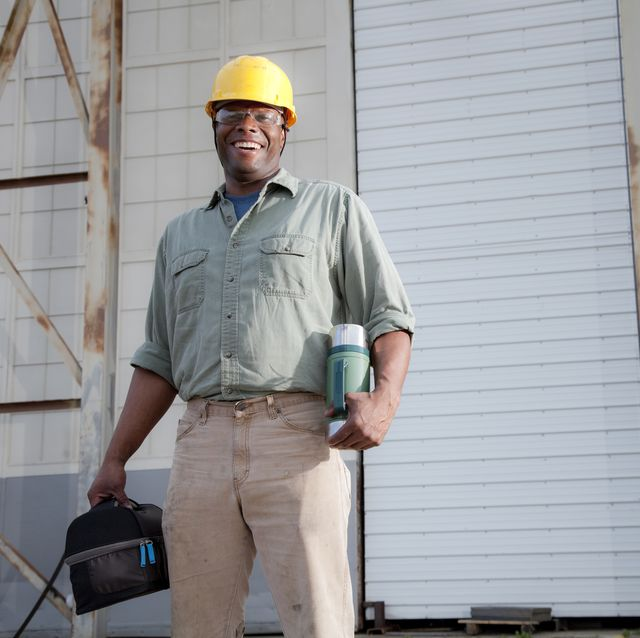 african american worker 30s with lunchbox and thermos, taking a break