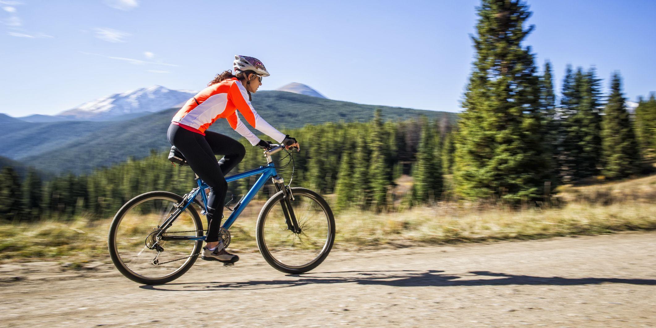 Hispanic woman riding dirt bike in rural landscape
