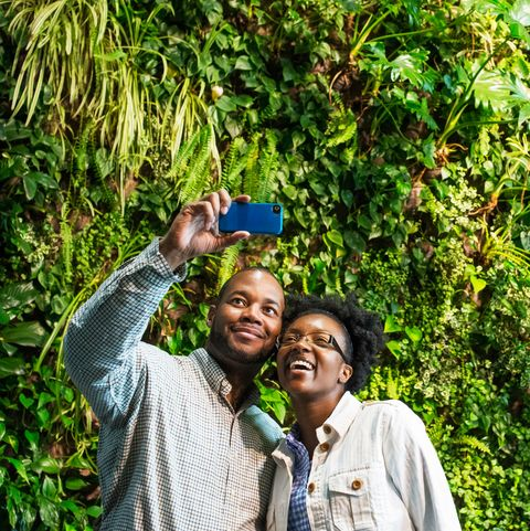 couple taking selfie in front of vegetation