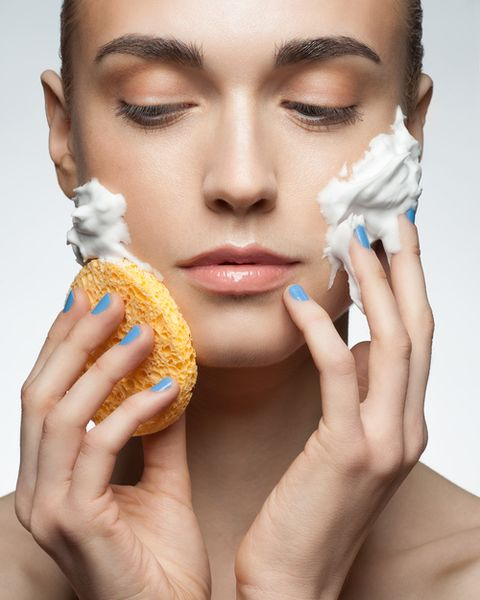 Woman washing her face with a yellow sponge
