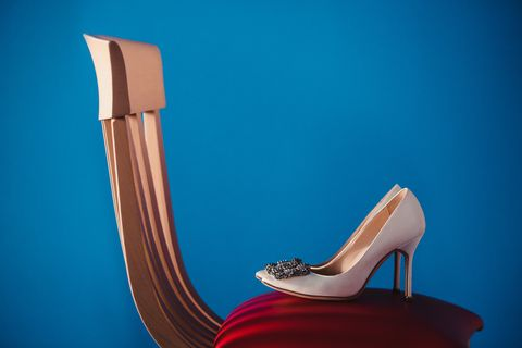 white bride's shoes on a red chair