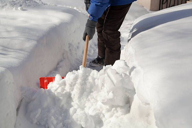 subject shoveling snow from the street sidewalk after the winter blizzard