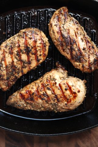 healthy eating  grilled skinless, boneless chicken breasts in a cast iron grilling pan