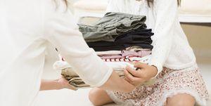 Children helps grandma by folding laundry