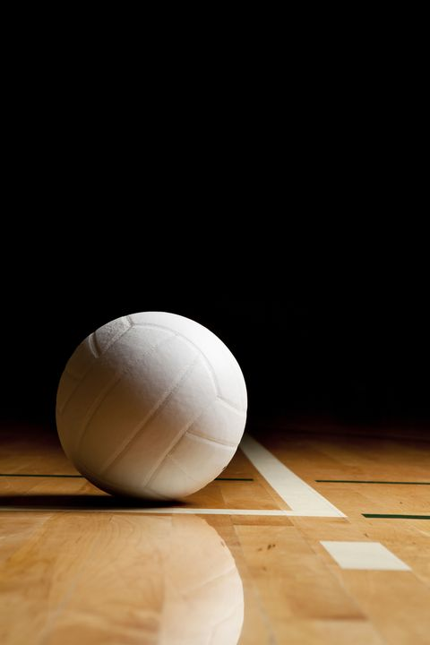 a white volleyball on the floor in a darkened gymsee my